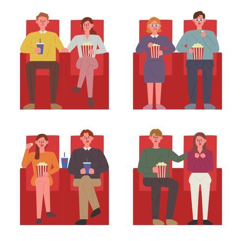 Casais sentados nas cadeiras vermelhas em um cinema assistindo a um filme.