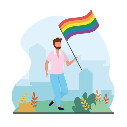 uomo con bandiera arcobaleno LGBTQ alla parata della libertà