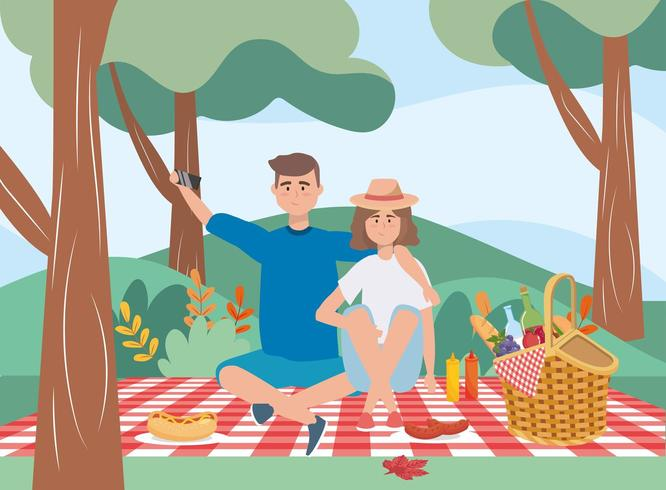 man and woman in the tablecloth with hamper and food