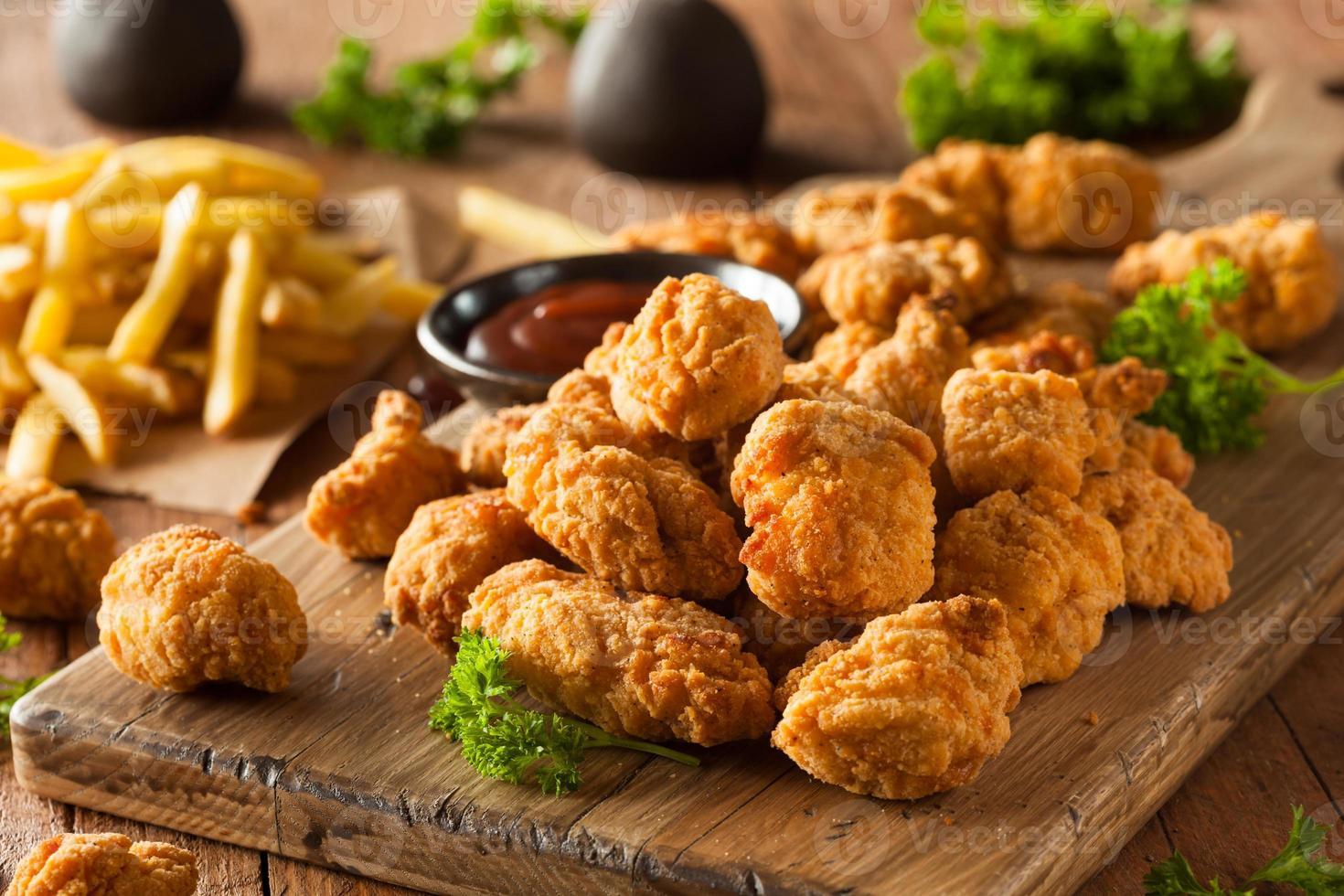 pollo crujiente casero de palomitas de maíz servido con papas fritas foto