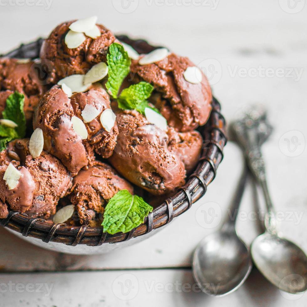 helado de chocolate con menta y almendras sobre fondo de madera foto