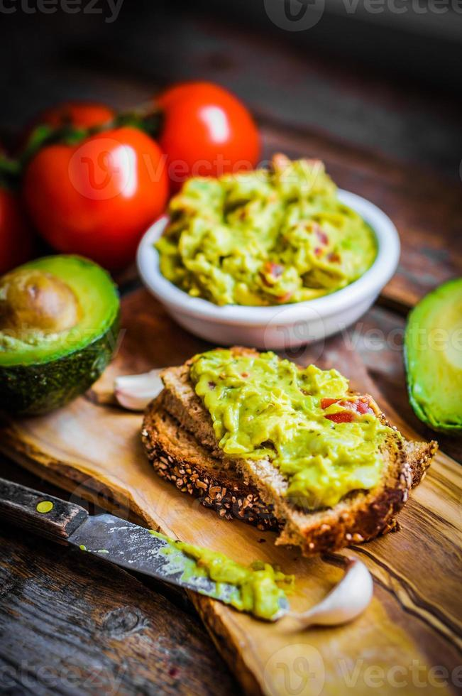 Guacamaole with bread and avocado on rustic wooden background photo