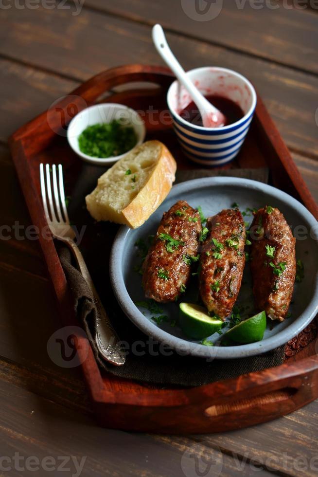 kebabs con salsa de bayas y cilantro en una bandeja vintage foto