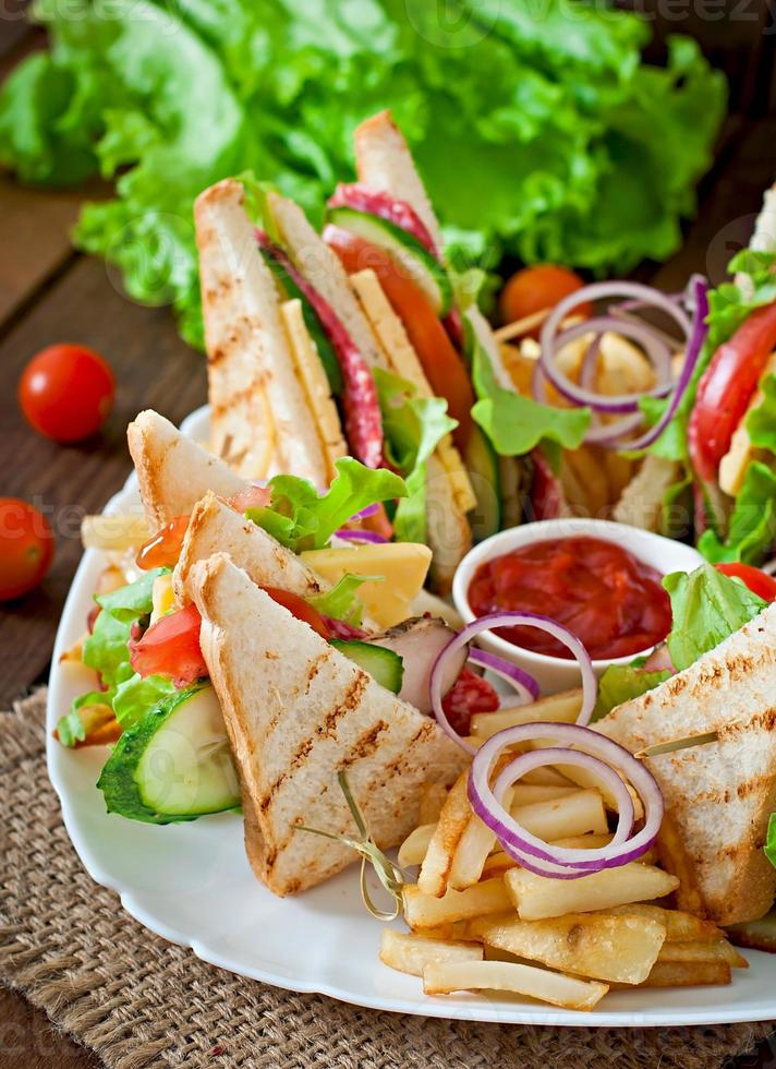 Club sandwich. Served with French fries. photo