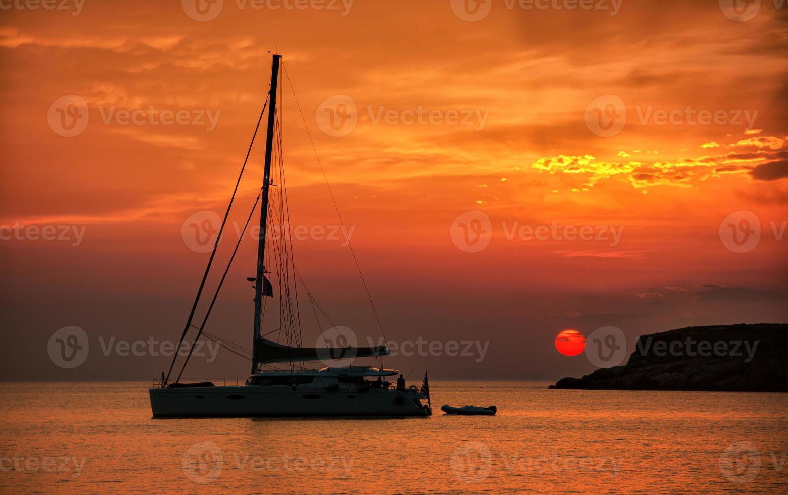 Silhouette of a sailing boat at sunset, in Syros Greece photo
