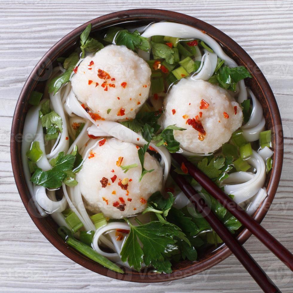 Sopa tradicional con bolas de pescado y fideos de arroz closeup. foto