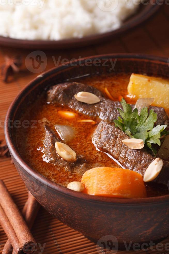 curry massaman tailandés con carne y maní macro. vertical foto