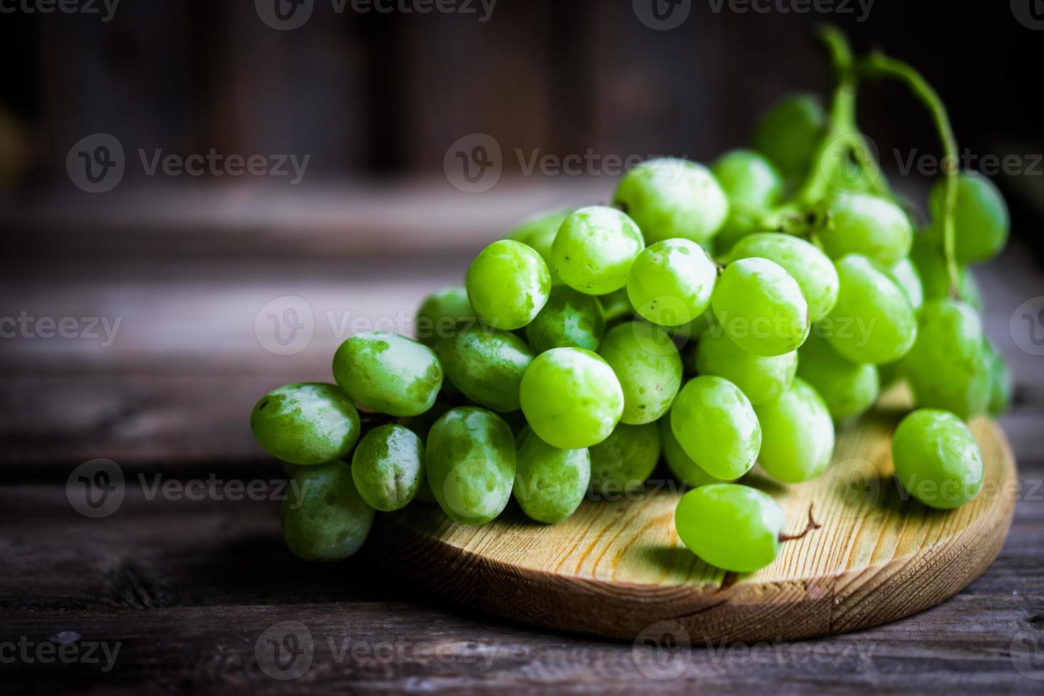 Vine of green grapes on rustic wooden background photo