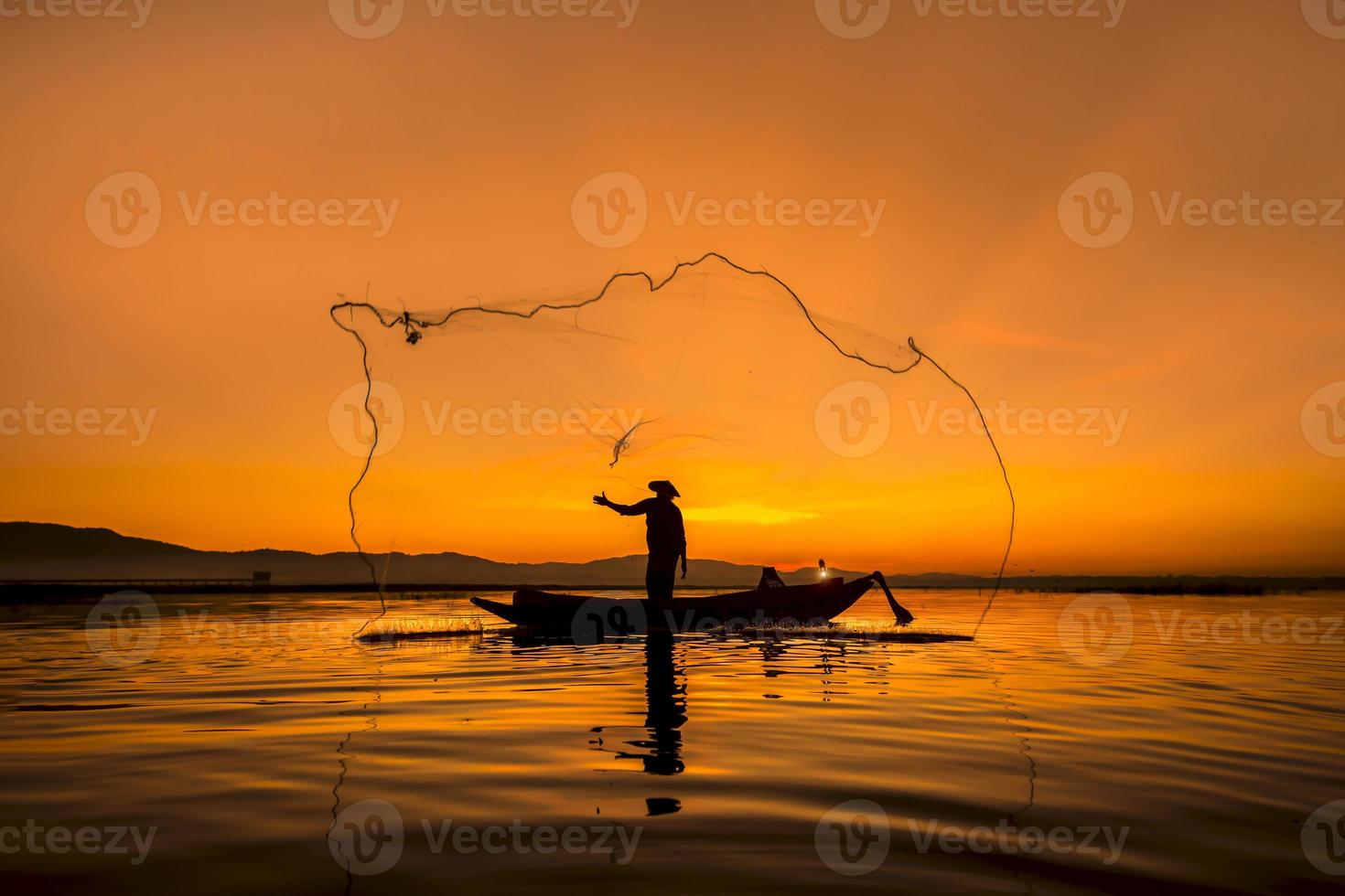 Fisherman of Bangpra Lake in action when fishing, Thailand. photo