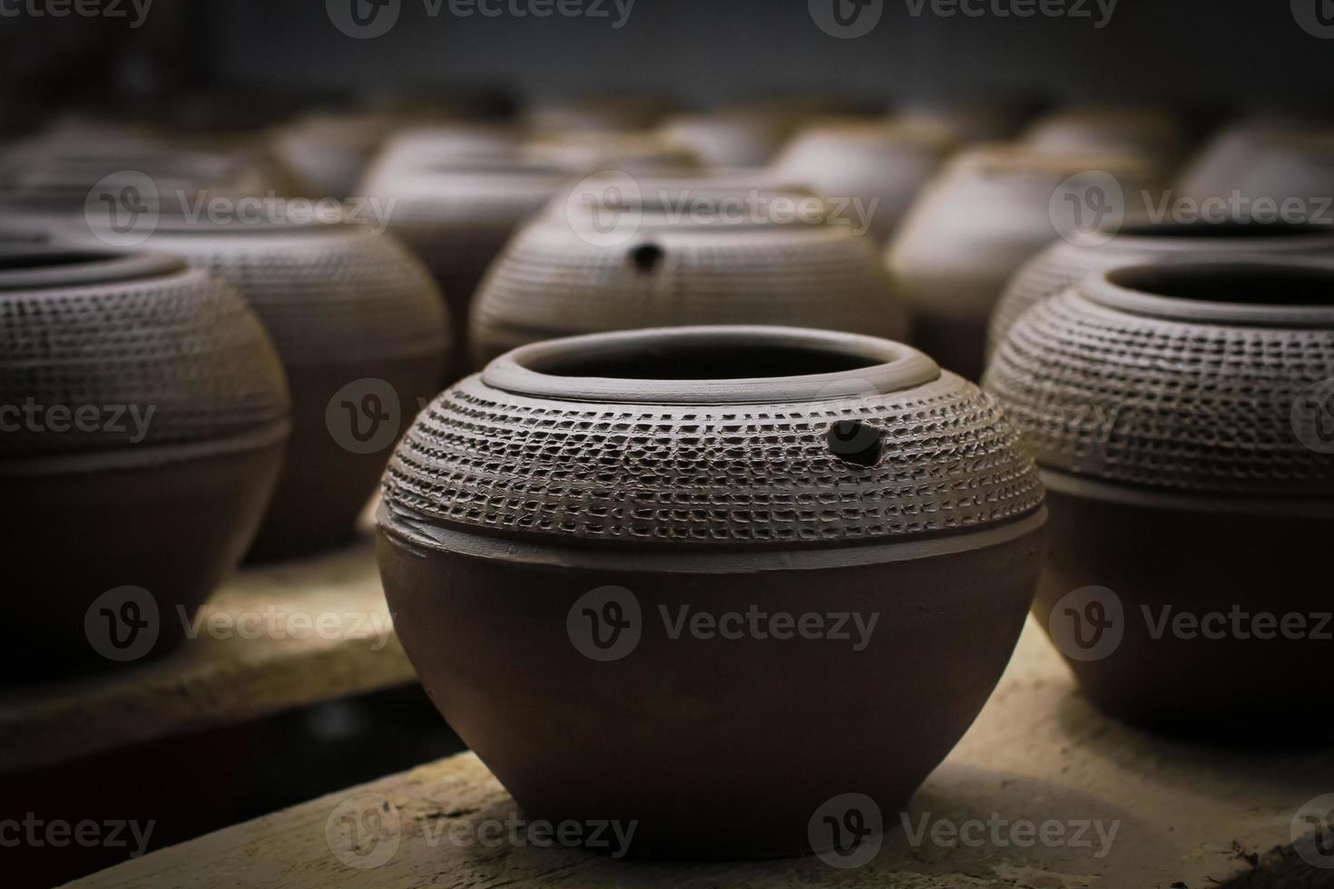 ollas de barro con motivos tallados en una fila foto