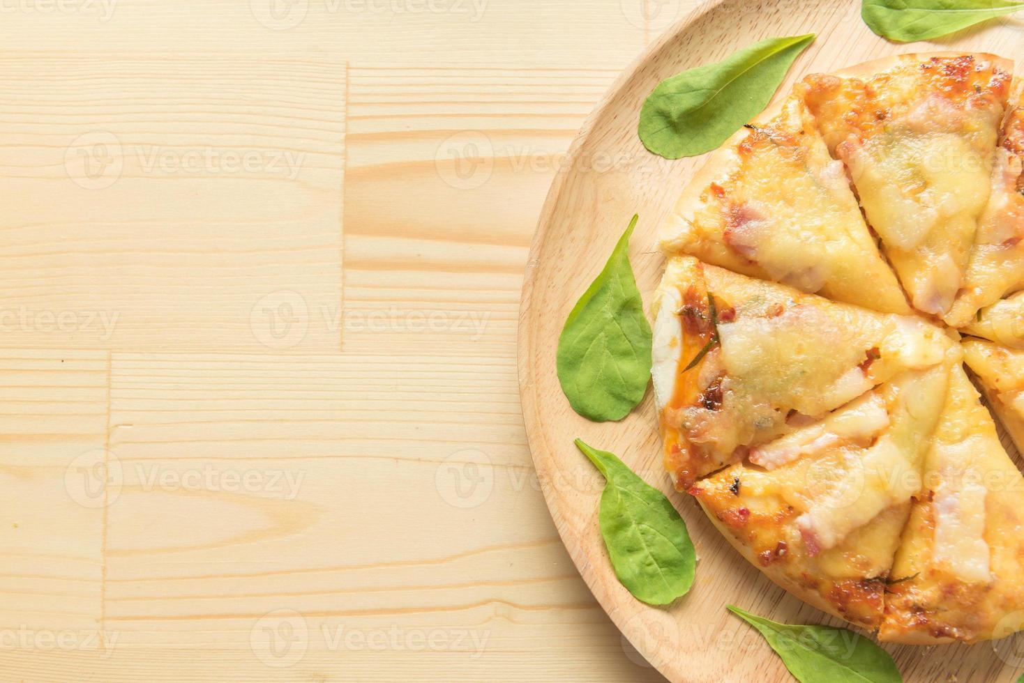 Rustic pizza on wooden background. Top view photo