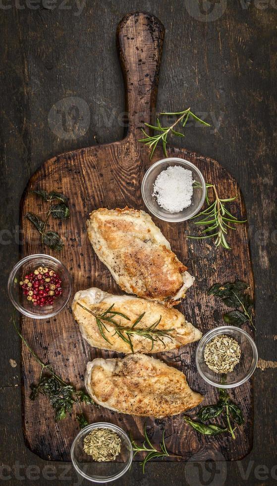 pechuga de pollo al horno picante sobre tabla de destripar de madera rústica, foto