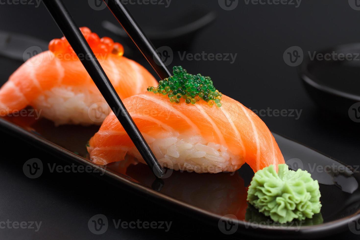 sushi de salmón nigiri en palillos sobre fondo negro foto