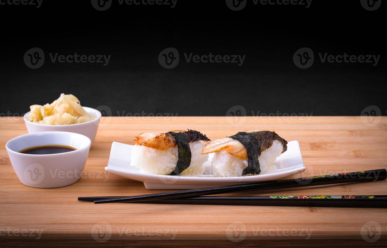 Two nigiri sushi eel with soy sauce on bamboo table photo