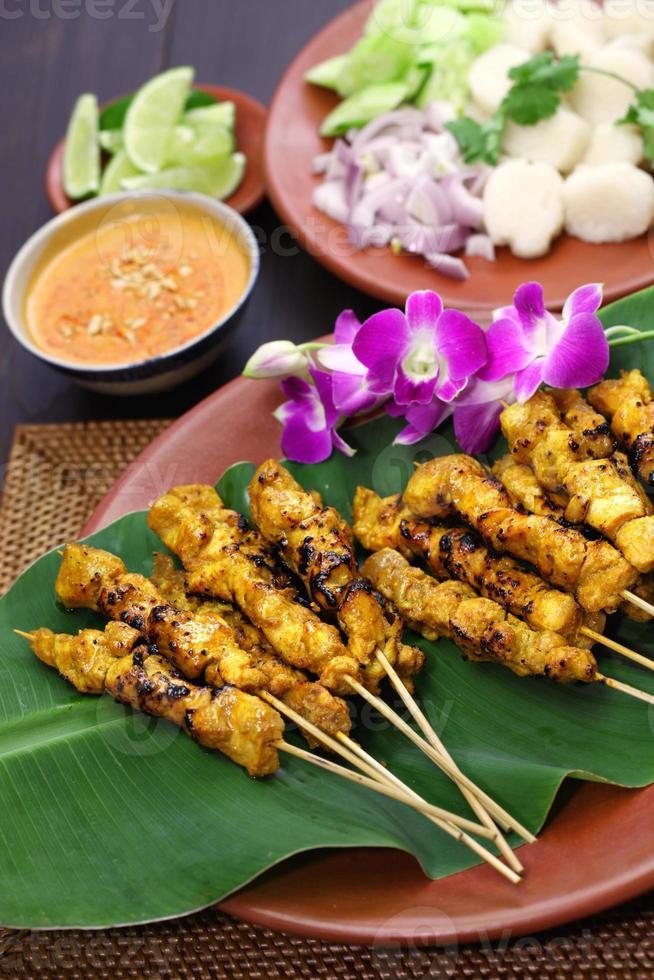 satay de pollo con salsa de maní, pinchos de cocina indonesia foto