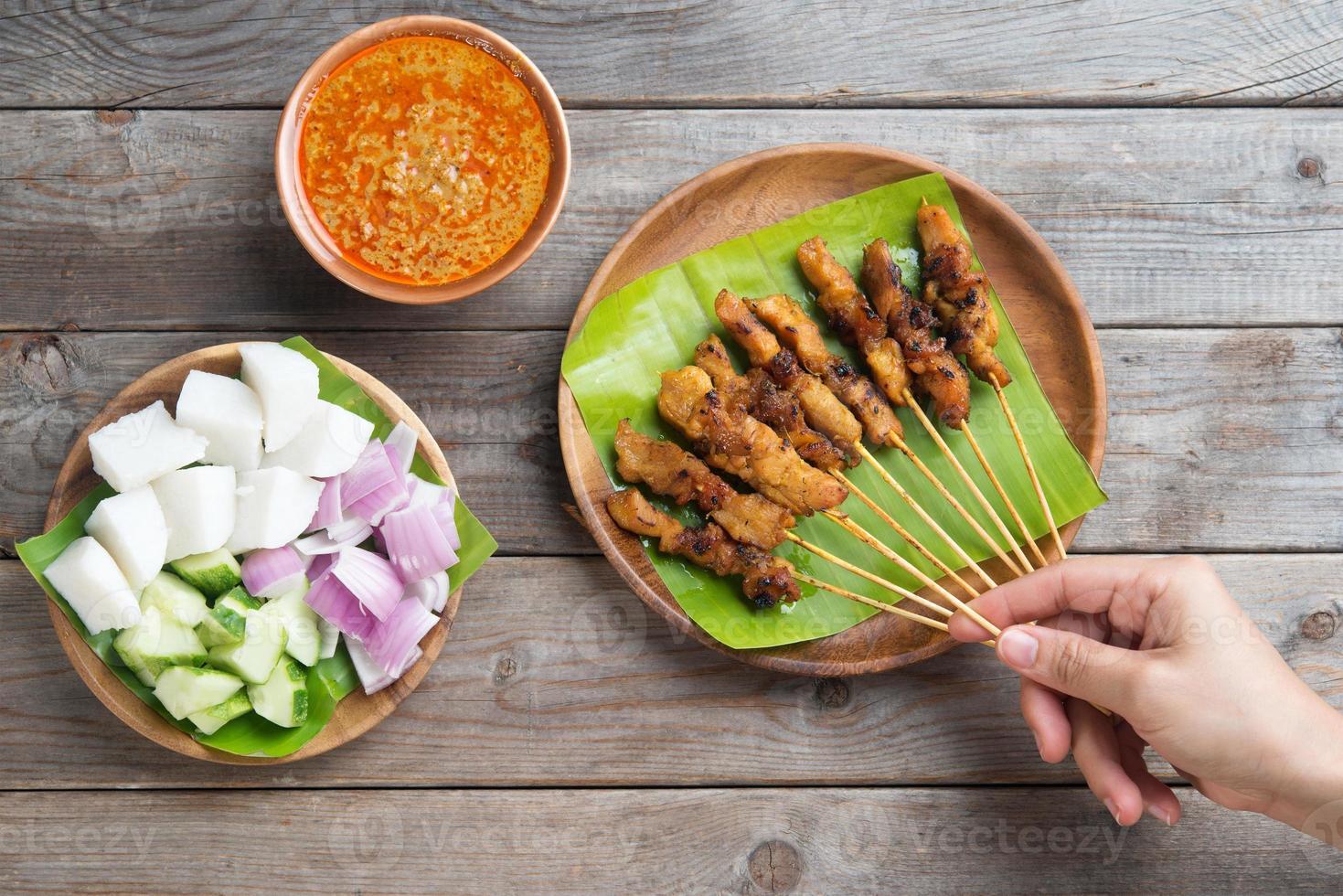 gente comiendo satay foto