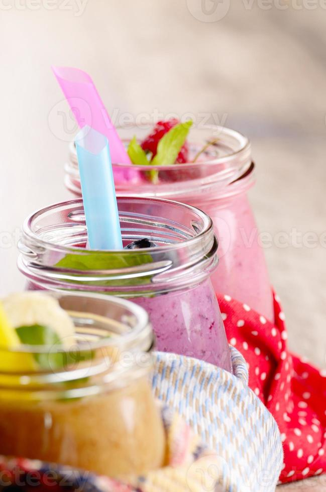 Assorted fruit shakes on white table photo