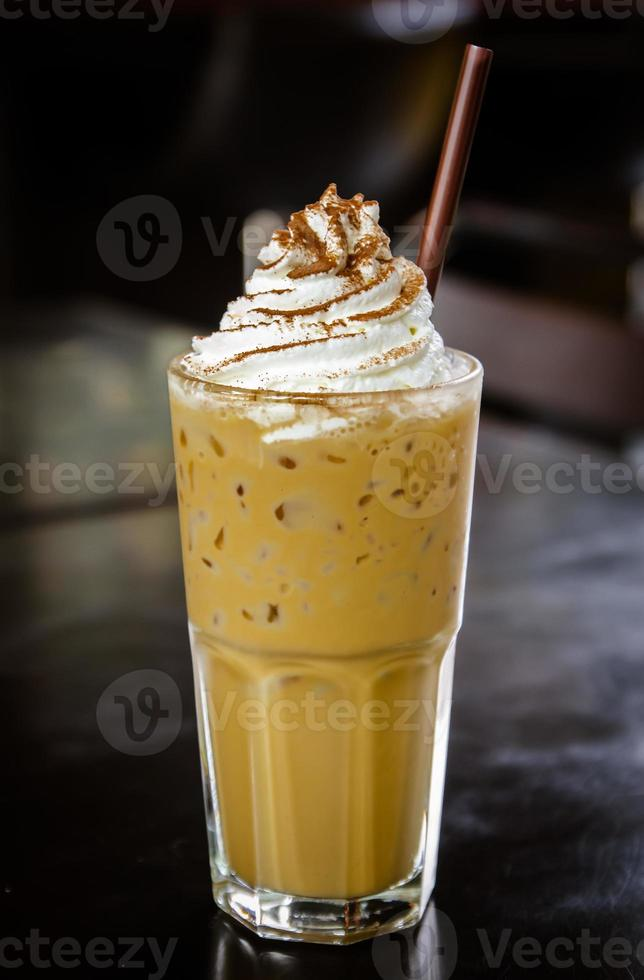 Iced coffee with whipped cream on the table. photo