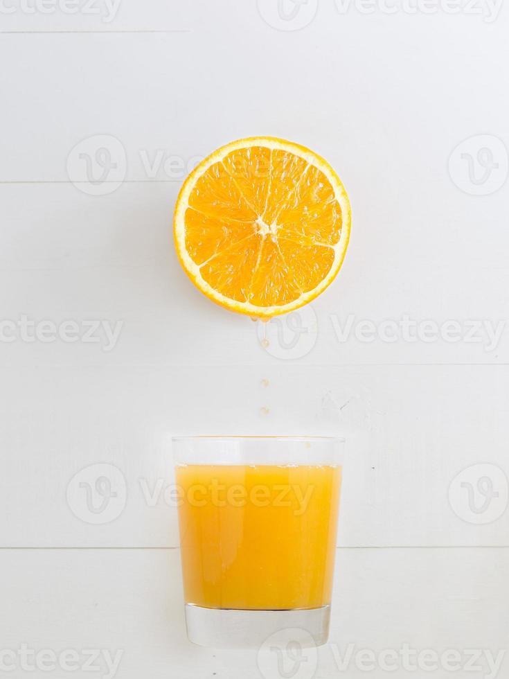 Orange dripping juice over a orange juice glass photo