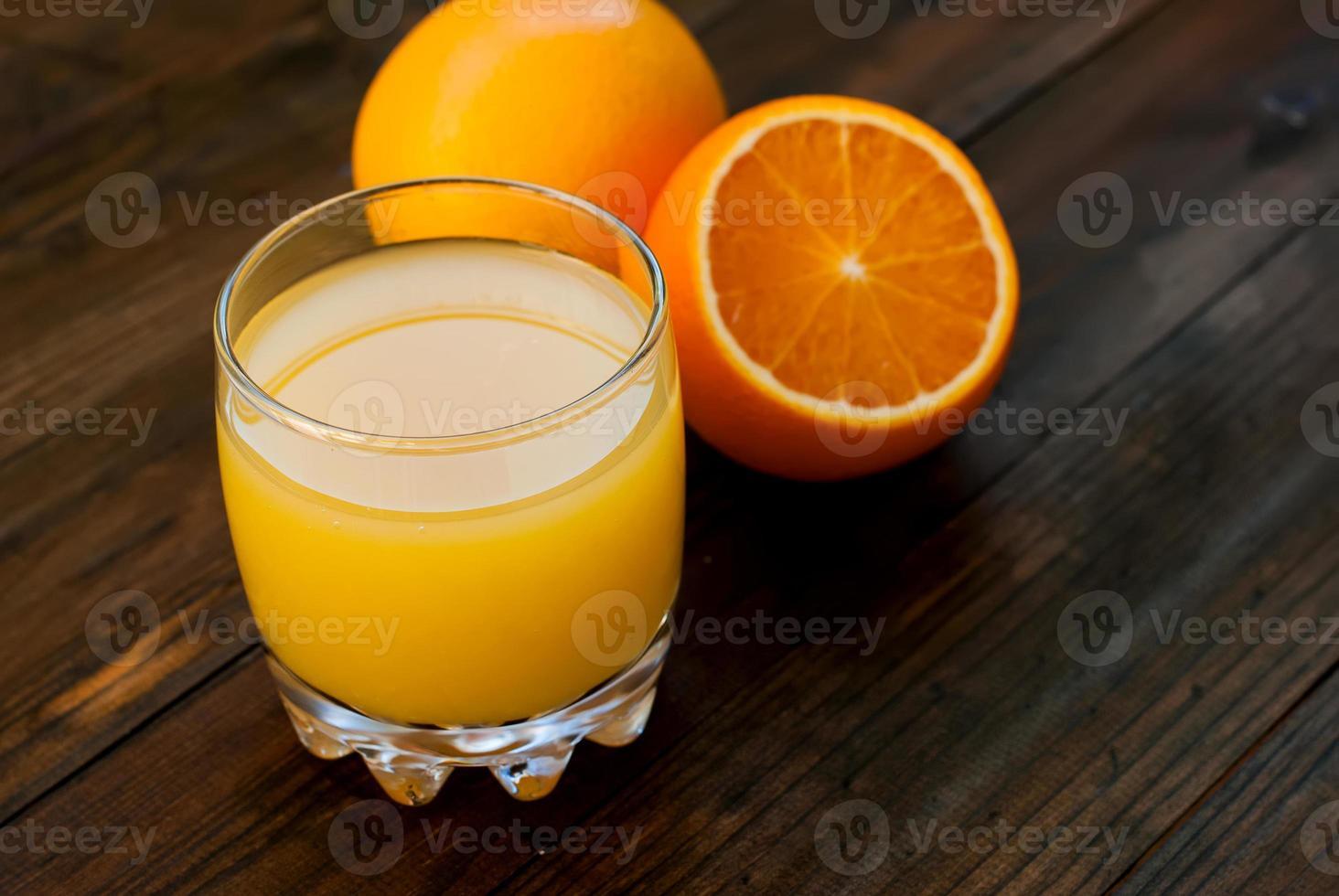 Fresh orange juice on wooden table photo