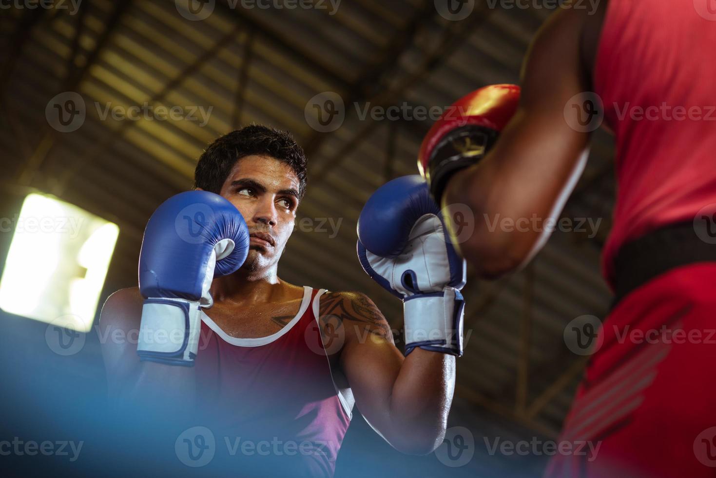 Vista desde el suelo de dos boxeadores masculinos en un ring de boxeo foto
