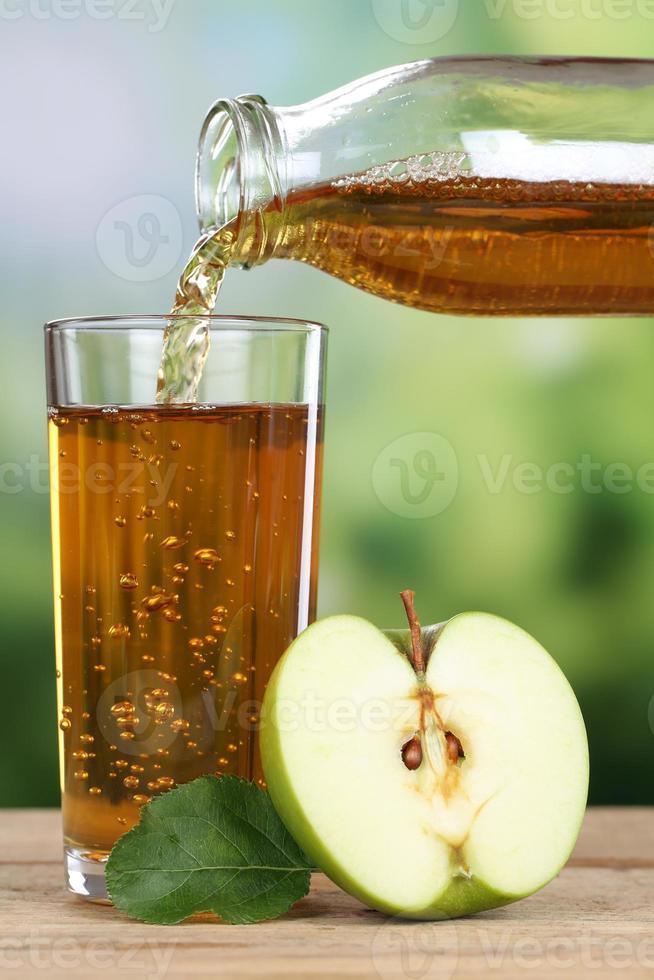 saludable beber jugo de manzana vertiendo de manzanas en un vaso foto