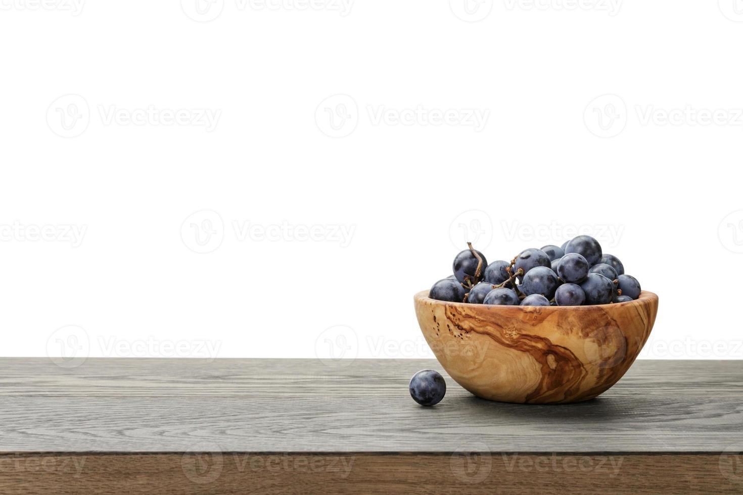 isabella uvas en un tazón de madera en la mesa, composición de borde foto