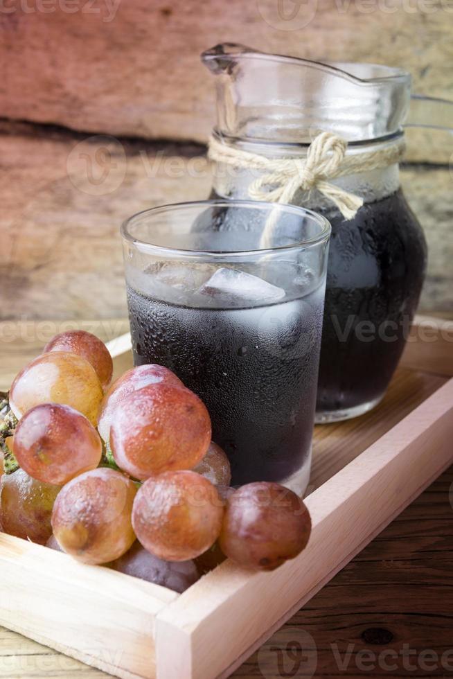 uvas frescas y jugo en mesa de madera foto