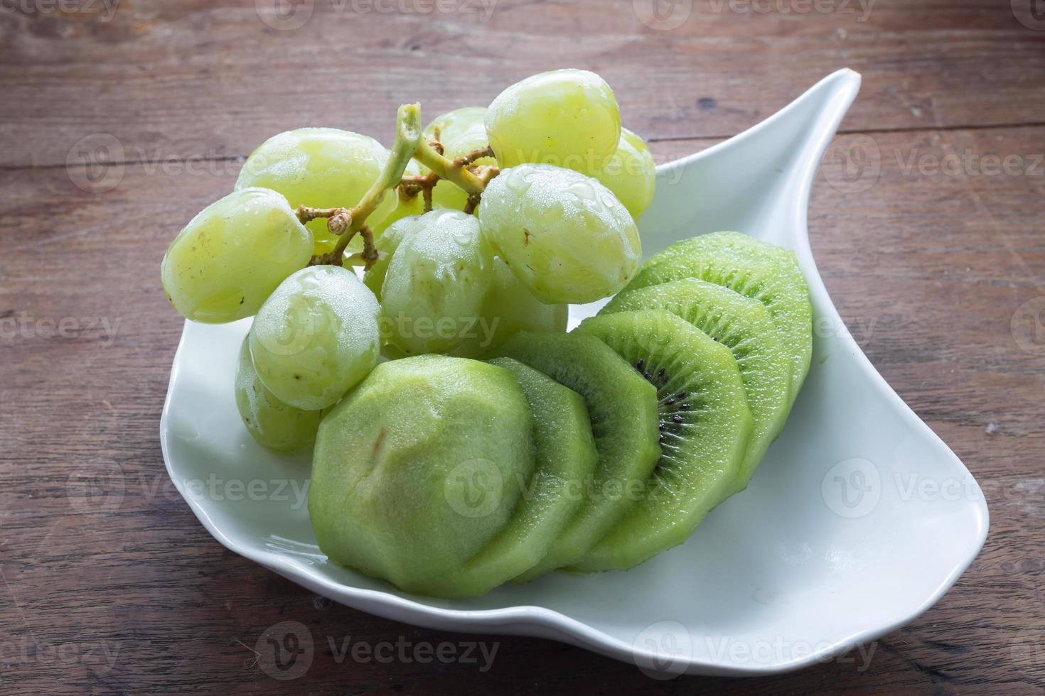 uva verde y kiwi en plato blanco foto