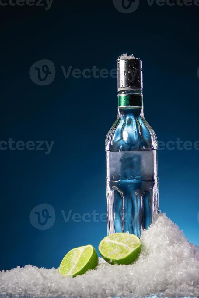 botella de vodka y rodaja de lima foto