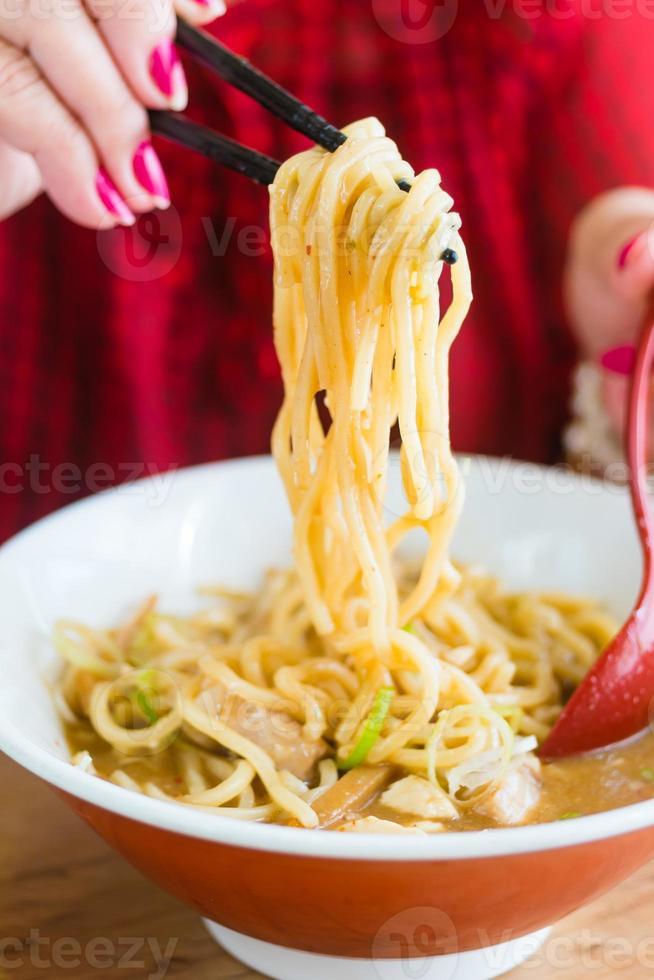 Mujer comiendo fideos estilo comida japonesa foto