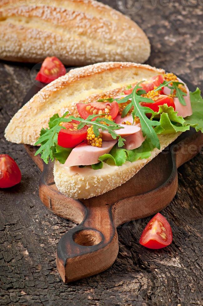Sandwich with sausage, lettuce, tomato and arugula photo