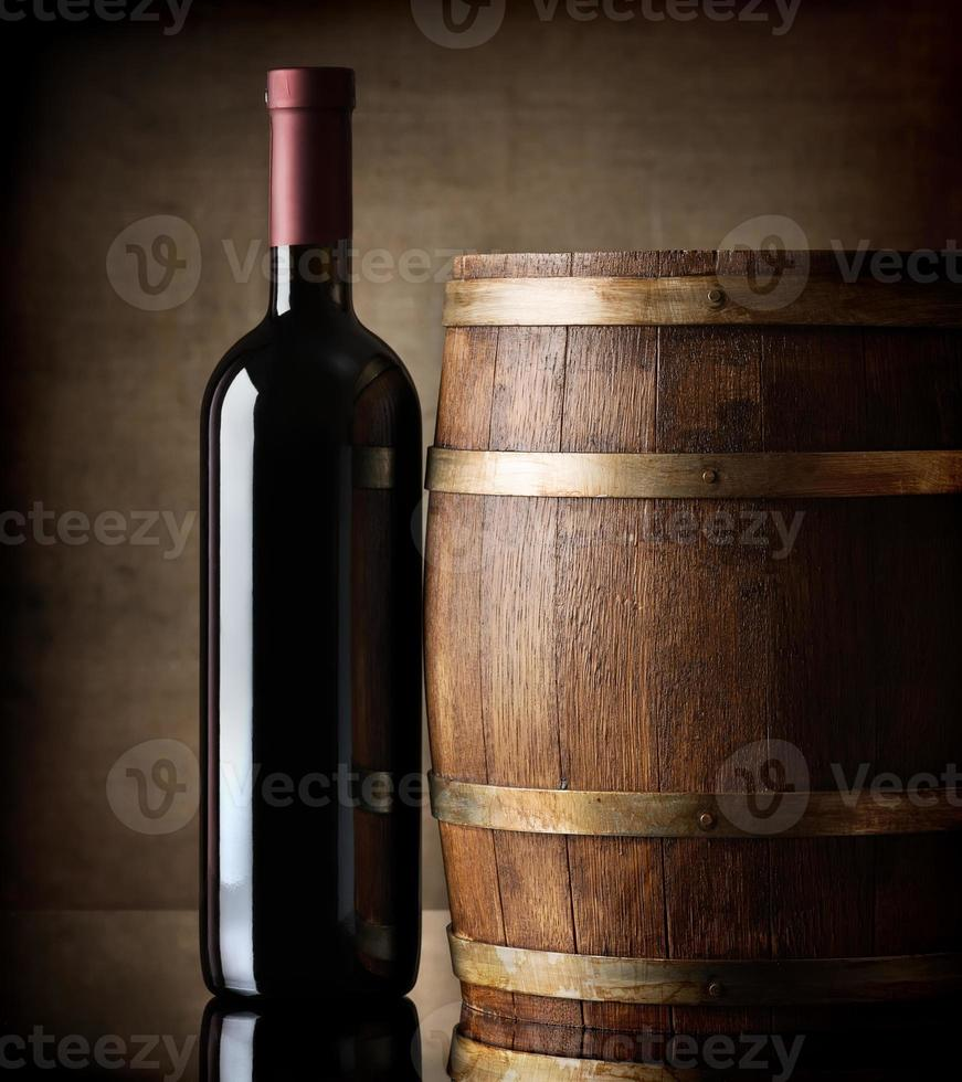 Bottle and wooden barrel photo