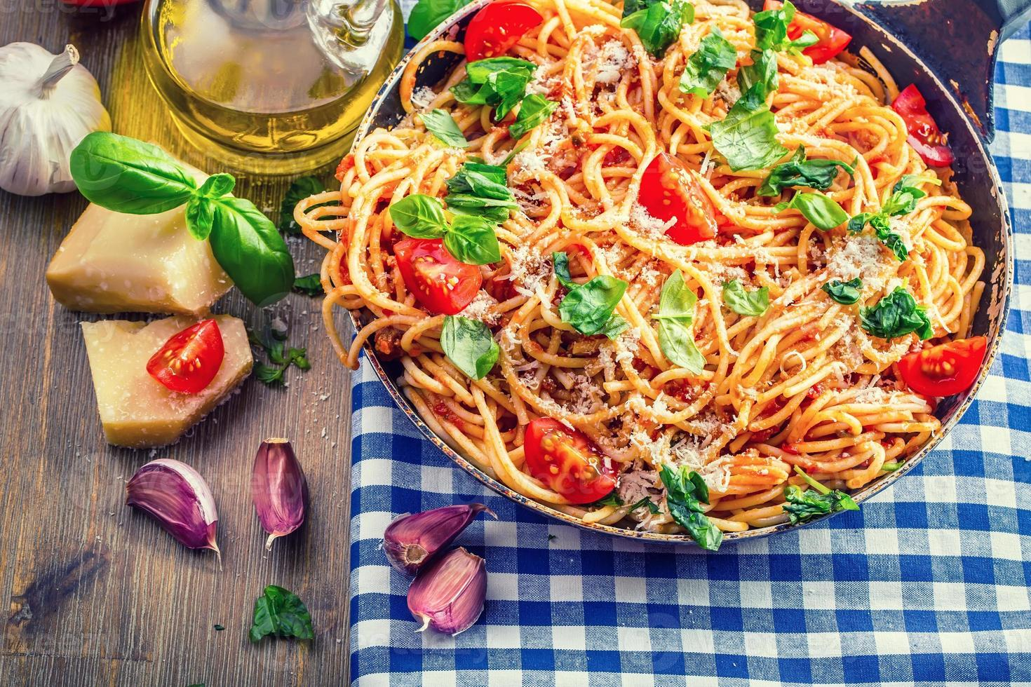 espaguetis a la boloñesa con tomate cherry y albahaca. foto