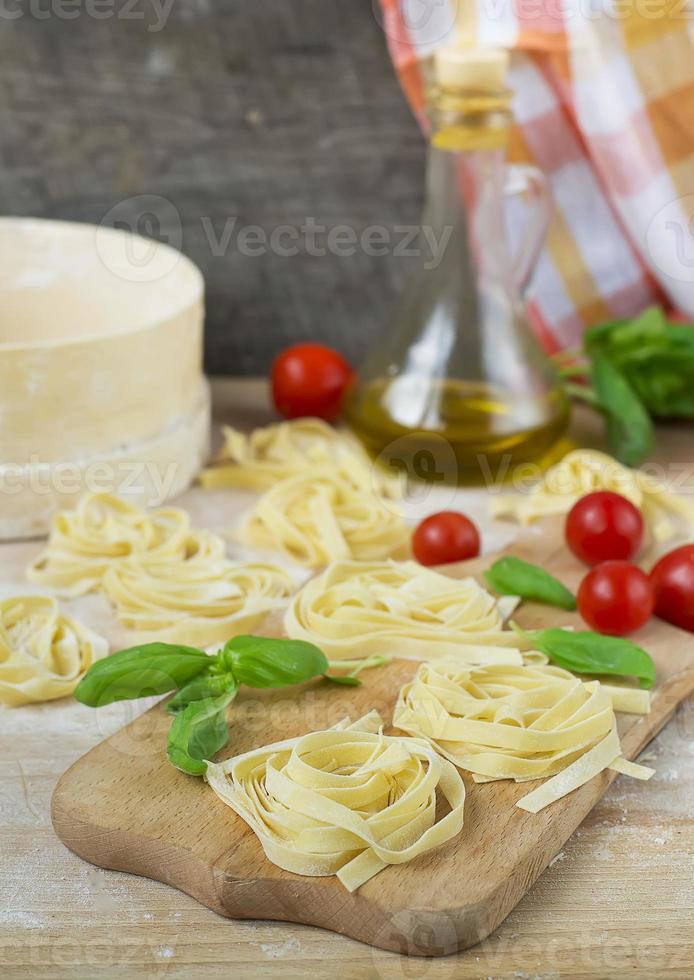 máquina de pasta fresca casera pasta, albahaca, tomates en madera foto