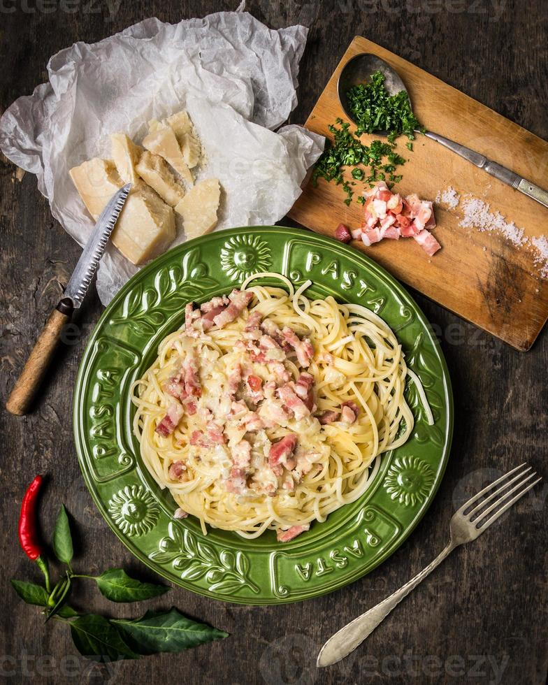 Pasta Carbonara in  green plate , parmesan, spices and seasonings photo