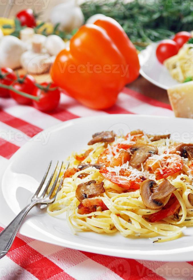 Pasta with shrimps and mashrooms on the wooden table photo
