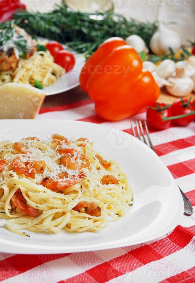 pasta con camarones y salsa en la mesa de madera foto
