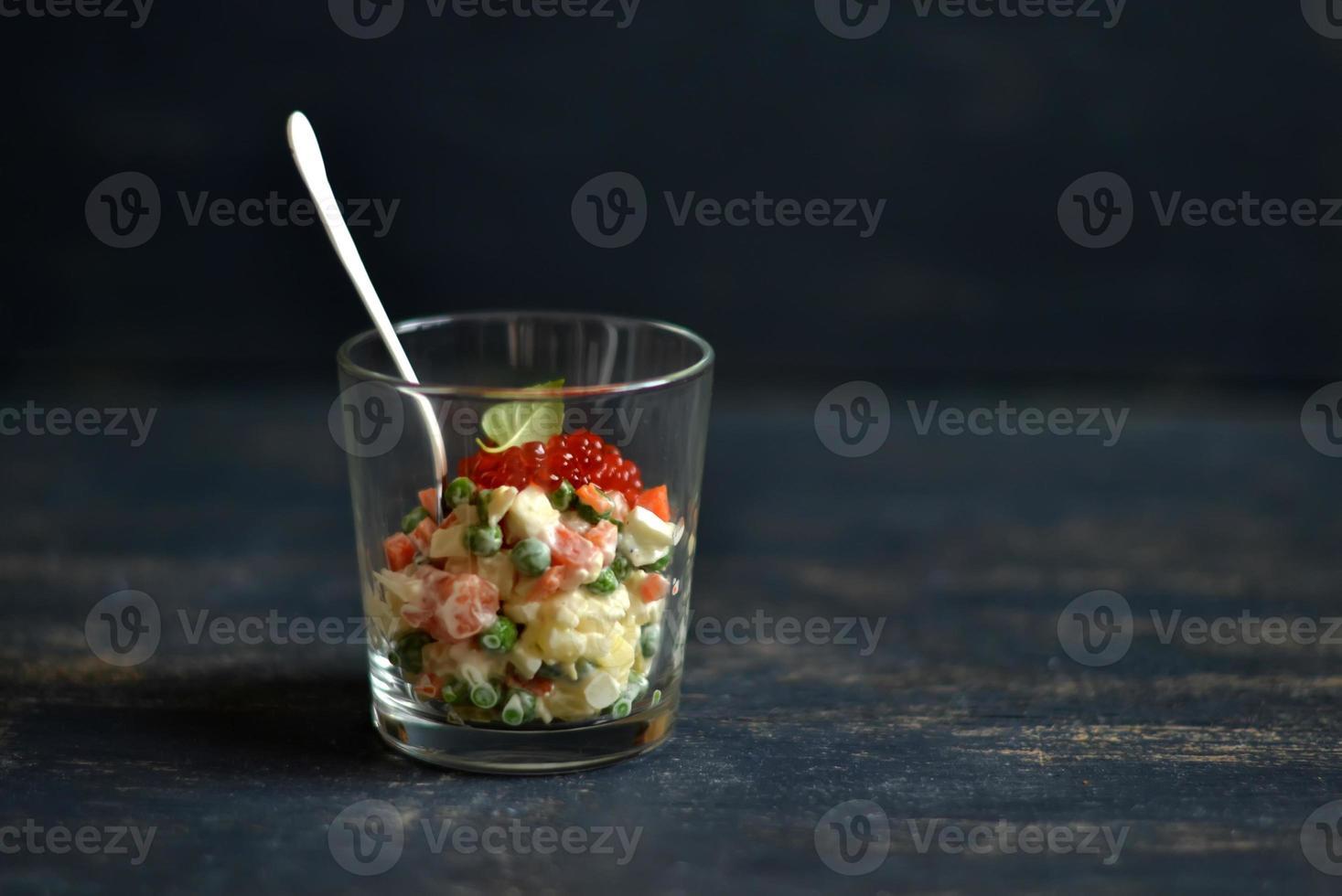 Ensaladilla rusa con salmón y caviar rojo sobre superficie azul foto
