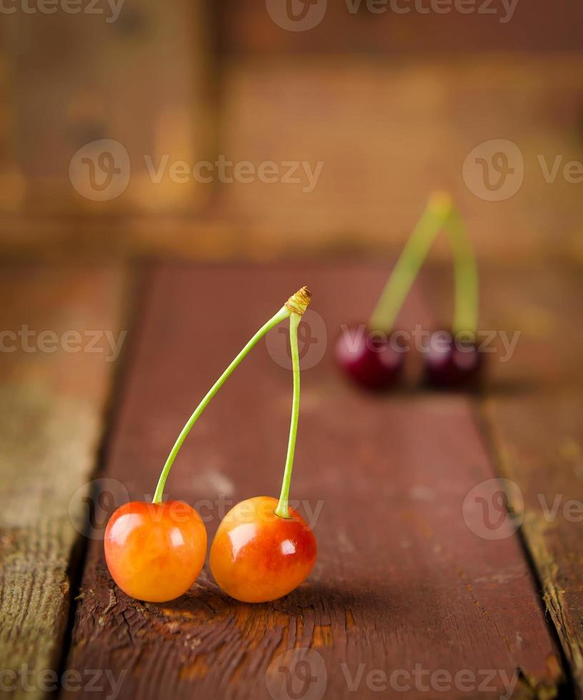 Red and yellow cherries on wooden background photo