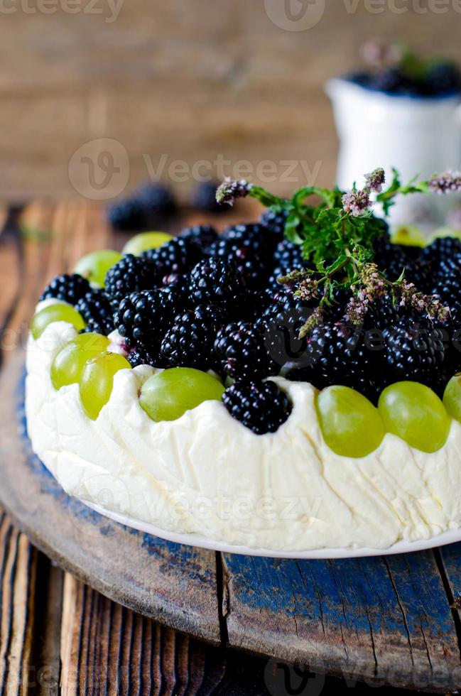 Cheesecake with blackberries and grapes on a wooden table old photo