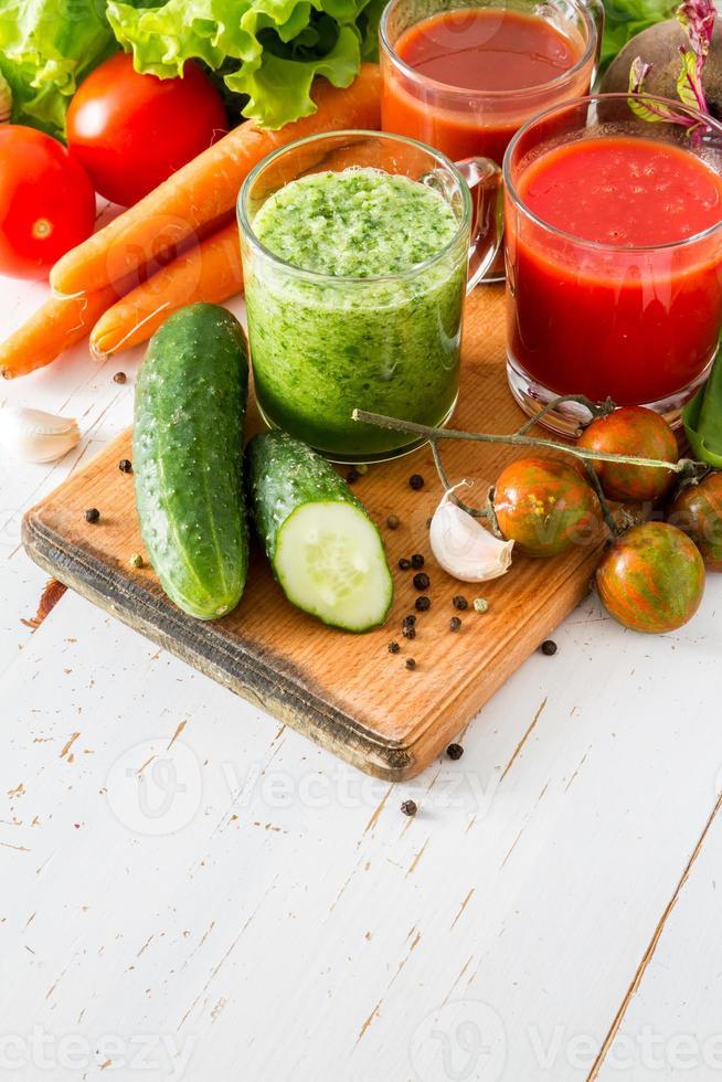 Selección de jugos e ingredientes vegetales, fondo de madera blanca foto
