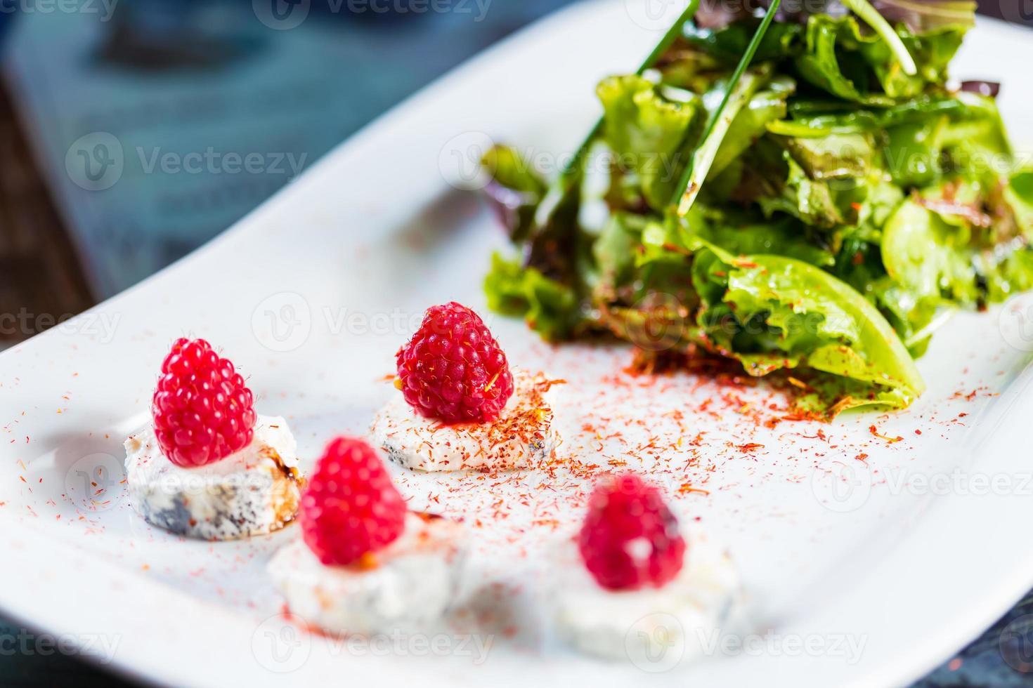 Ensalada fresca con queso de cabra y frambuesa. foto