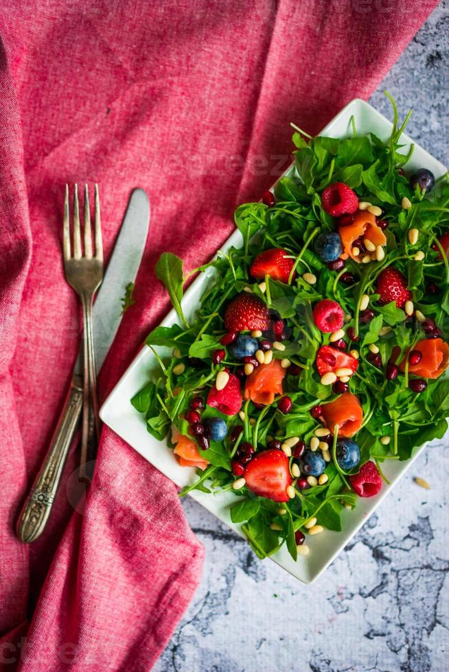 Healthy salad with arugula,spinach,smoked salmon and berries photo