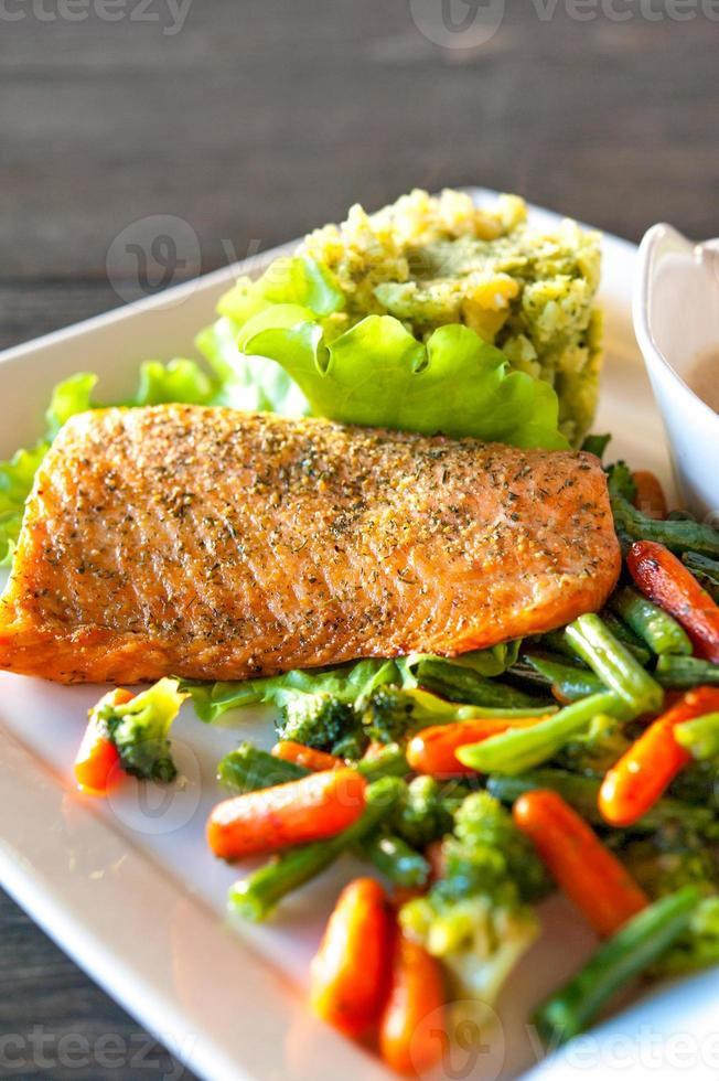 Grilled salmon fillet with potato-spinash mash and vegetables. photo