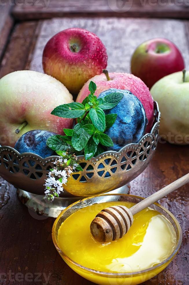 manzanas y ciruelas en florero de hierro foto