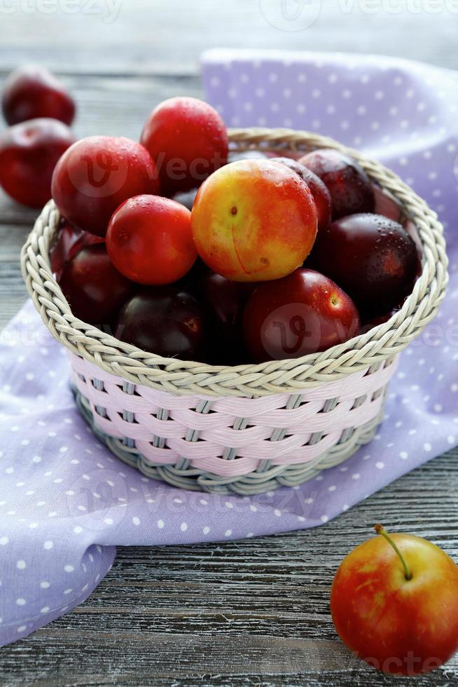 ripe plums in a round basket photo