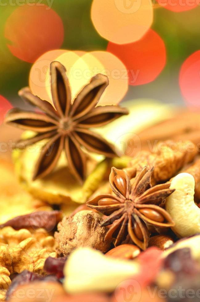 christmas spices, nuts, cookies and dried fruits on bokeh background photo