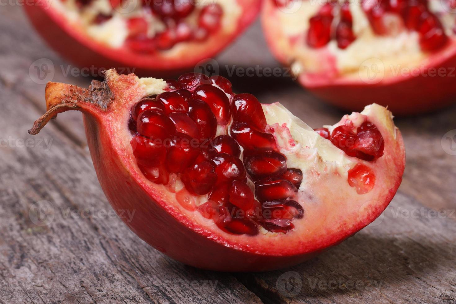 ripe pomegranate on an old wooden table closeup. macro photo