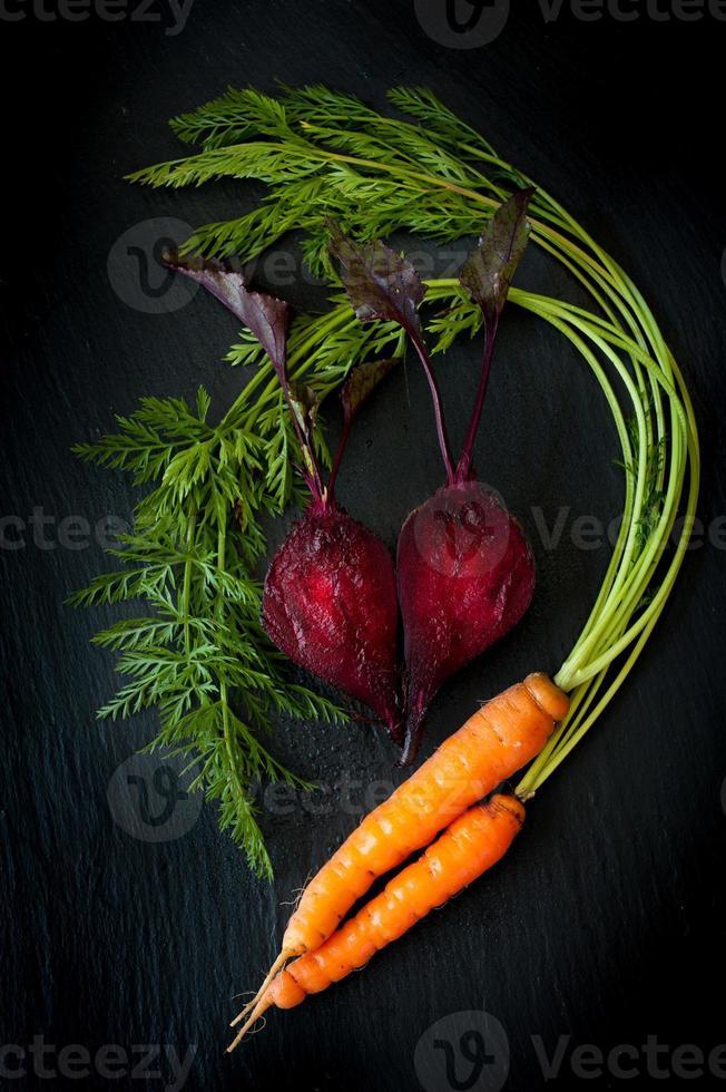 remolacha y zanahorias en pizarra pizarra negra foto